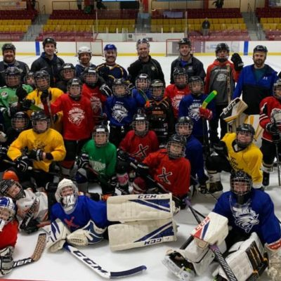 Young children who participated in the hockey camp take a team photo with their coaches